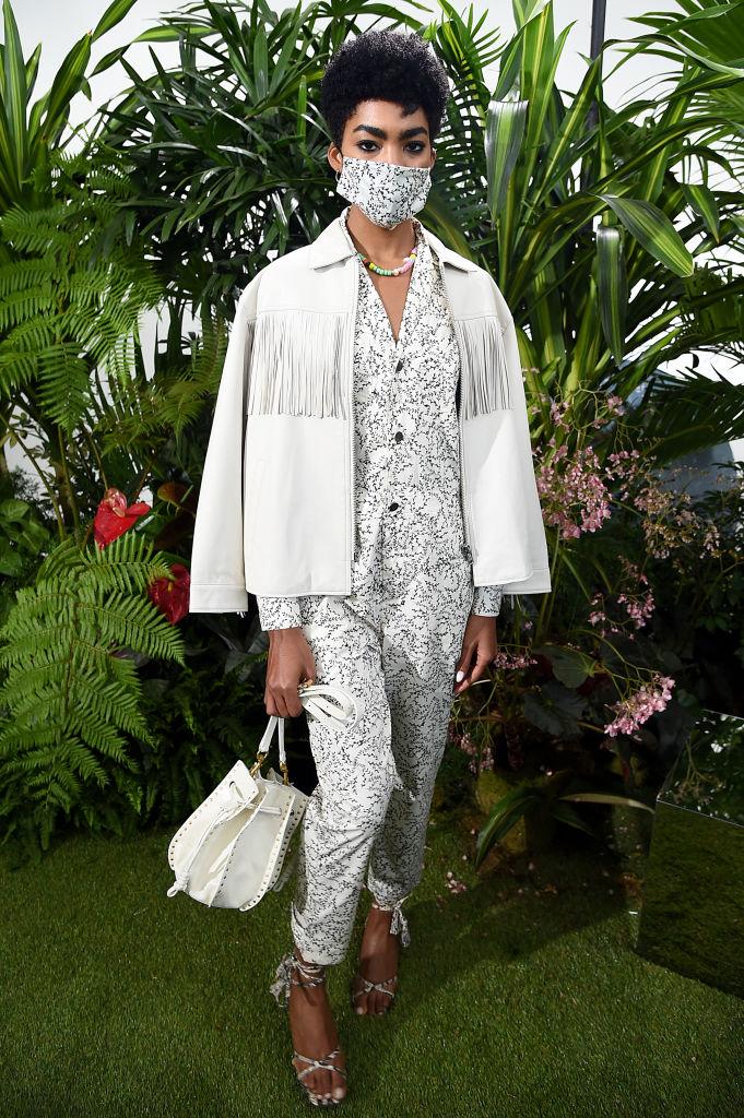 Modelo posando com jaqueta branca de couro com franjas, última tendência da moda do outono.