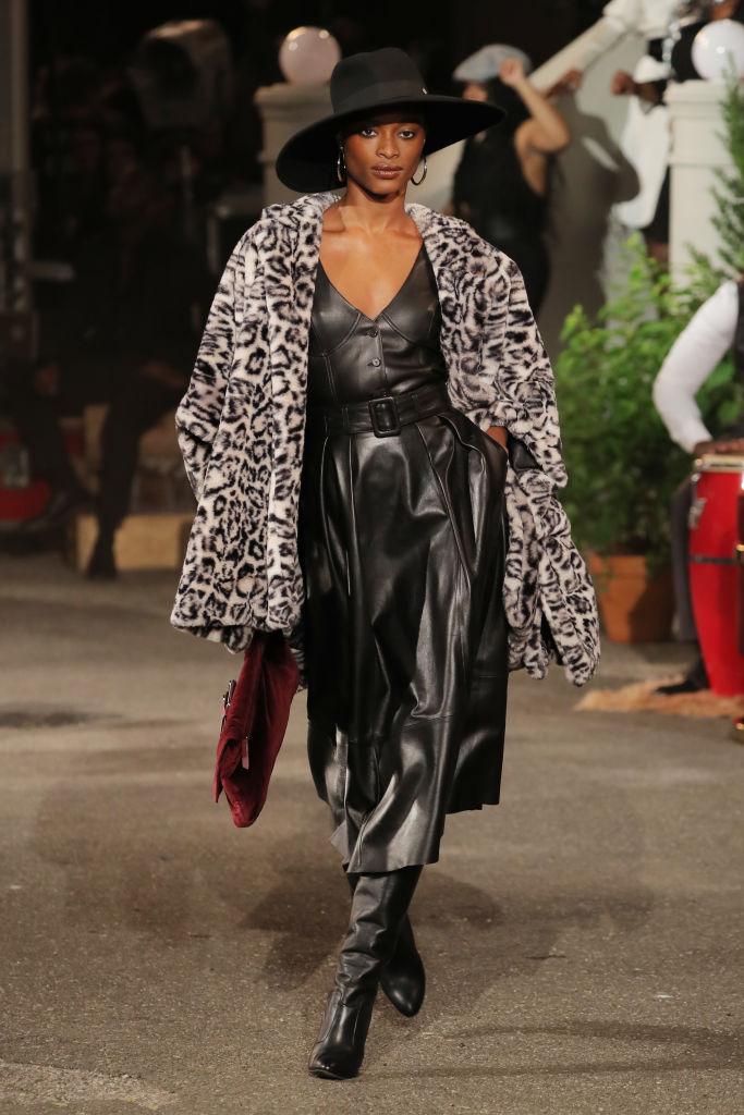 Modelo desfilando na passarela de outono com última tendência, casaco de oncinha.