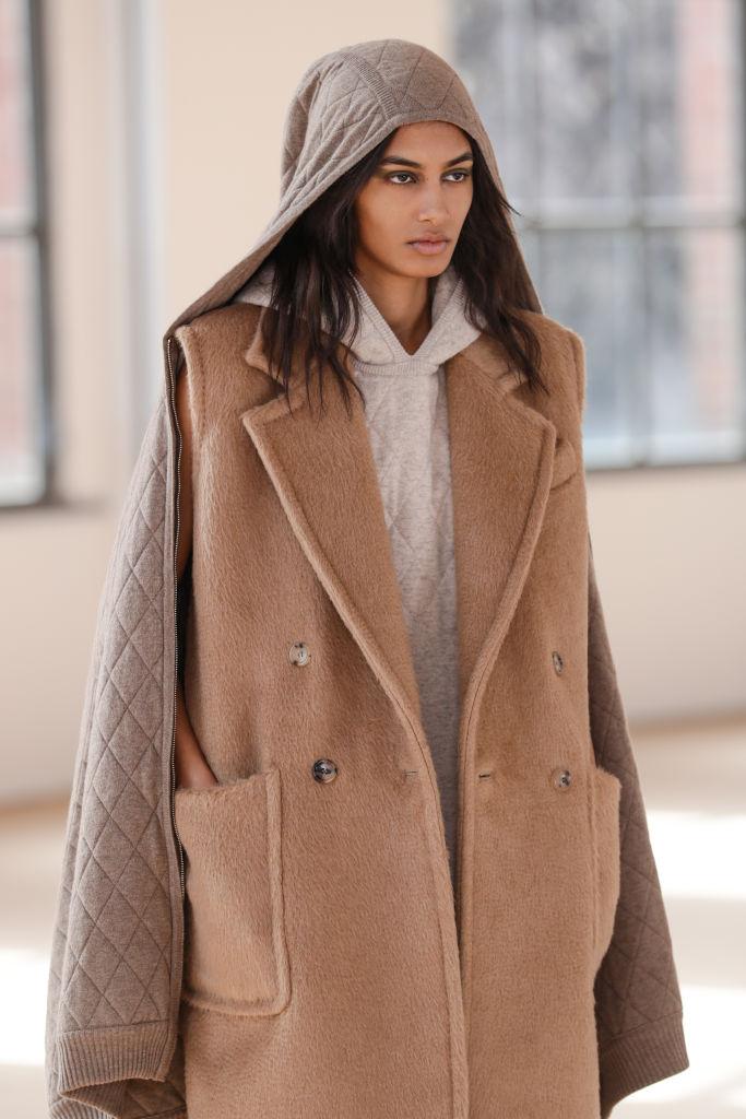 Modelo desfilando com look tendência: monocromático com toques de marrom e tons terrosos.