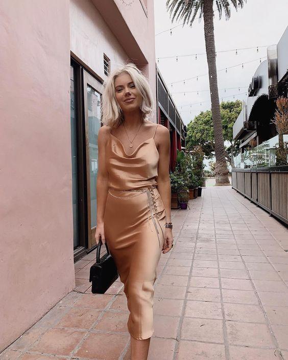 Mulher com slip dress na cor champagne.